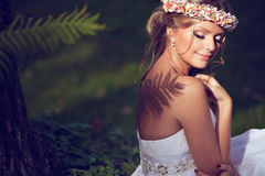 Portrait of a beautiful bride with a diadem of flowers on the he. Ad with Nude shoulders, on which falls the shadow of a fern Royalty Free Stock Photography