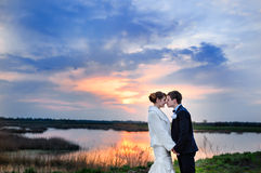 Portrait of beautiful bride and groom hugging and looking at lake at sunset Stock Photos
