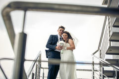 Portrait of beautiful bride and groom hugging on staircase Stock Photo