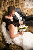 Portrait of beautiful bride and groom kissing on stack of hay Stock Images