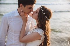 Portrait of beautiful bride and groom on ocean beach. Young couple of newlyweds looking at each other in love. Concept honeymoon, just married royalty free stock photo