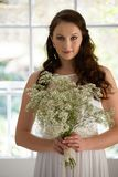 Portrait of beautiful bride holding bouquet while standing at home. Portrait of beautiful bride holding bouquet while standing against window at home Royalty Free Stock Photos