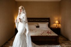Portrait of a beautiful bride in a lace wedding dress and a long veil, in hotel room. Next to a large bed Stock Images
