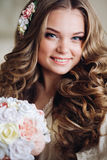 Portrait of beautiful bride with long hair in white lingerie looking at the camera, smiling. Royalty Free Stock Photos