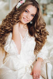 Portrait of beautiful bride with long hair in white lingerie looking at the camera, smiling. Stock Images