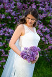 Portrait of beautiful bride with long veil standing near lilac. Portrait of young beautiful bride with long veil standing near lilac tree Royalty Free Stock Photo