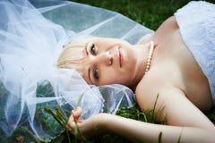 Portrait beautiful bride lying on grass Stock Photography
