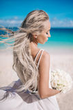 Portrait of the beautiful bride in a open back white wedding dress stand on the beach with white bouquet. Hair streams in the wind Stock Image