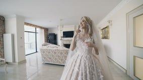 Portrait of beautiful bride rejoicing in wedding dress in room. 4K stock video footage