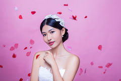 Portrait of beautiful bride with rose petals in mid-air against pink background Royalty Free Stock Photography