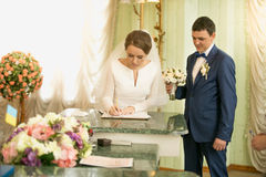 Portrait of beautiful bride signing wedding license at registry Stock Photo