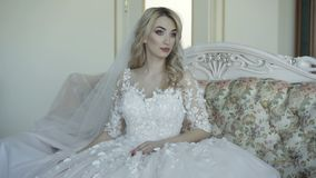 Portrait of beautiful bride sits on sofa, smiles and looks at camera. 4K stock video footage
