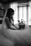 Portrait of beautiful bride sitting on bed at house Royalty Free Stock Images