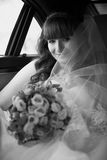 Portrait of beautiful bride sitting in car and holding bouquet Royalty Free Stock Photos