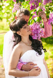 Portrait of beautiful bride smelling lilac flowers with groom Royalty Free Stock Photo