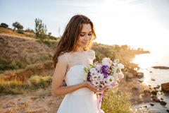 Portrait of beautiful bride standing by the beach Stock Photo