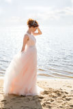 Portrait of beautiful bride standing by the beach at sunset Stock Photography