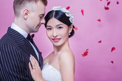 Portrait of beautiful bride standing with groom against pink background.  Royalty Free Stock Photo