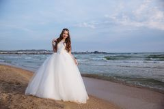 Portrait of beautiful bride in stylish wedding dress on ocean beach. Bride with hairstyle and makeup posing on wedding royalty free stock photos