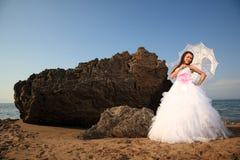Bride with umbrella Stock Images