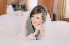 Portrait of beautiful bride in veil with curly hairstyle lying on bed.  Royalty Free Stock Image