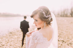 Portrait of beautiful bride wearing white dress and veil with groom standing in background near river. Portrait of beautiful bride in white dress and veil with Stock Photography