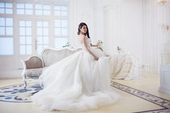 Portrait of beautiful bride. Wedding dress with open back. Luxurious light interior Royalty Free Stock Images