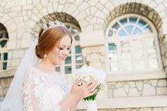 Portrait of a beautiful bride in a white dress and a bouquet of flowers in her hands royalty free stock photo