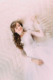 Portrait of beautiful bride in white dress and veil on bed in wedding day.  Royalty Free Stock Photos