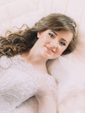 Portrait of beautiful bride in white dress and veil on bed in wedding day.  Stock Images