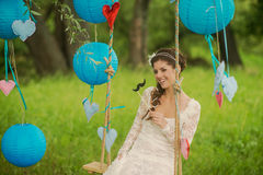 Portrait of a beautiful bride in white wedding. Gorgeous bride on the decorated swing on the tree Stock Images