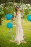 Portrait of a beautiful bride in white wedding. Gorgeous bride on the decorated swing on the tree Stock Photos