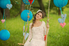 Portrait of a beautiful bride in white wedding. Gorgeous bride on the decorated swing on the tree Royalty Free Stock Photos