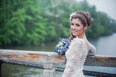 Portrait of a beautiful bride in white wedding. Gorgeous bride on a wooden bridge in the rain Royalty Free Stock Image