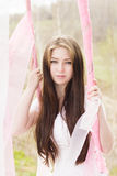 Portrait of beautiful bride woman in all white outdoors pink swing Royalty Free Stock Photo