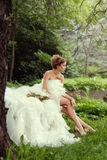 Portrait of a beautiful bride woman sits in a profile and looks into the distance. Portrait of a beautiful bride woman sits in a profile and looks into the Royalty Free Stock Images