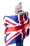 Portrait of a beautiful British girl smiling holding up the UK flag. Isolated on white. Stock Photo