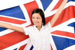 Portrait of a beautiful British girl smiling holding up the UK flag, looking away. Royalty Free Stock Image
