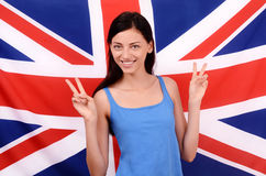 Portrait of a beautiful British girl smiling and signing victory. Stock Images