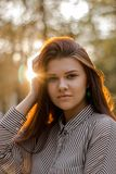 Portrait of a beautiful brown-haired girl whose sunset sunlight shimmers in her hair. A young lady with a confident smile looks straight stock photo