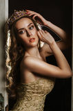 Portrait of a beautiful brown-haired woman in a gold dress and crown. Stock Images