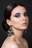 Portrait of beautiful brunet woman. With blue earrings Stock Photo