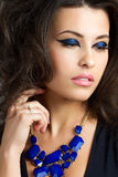 Portrait of beautiful brunet woman. With blue necklace Stock Photography