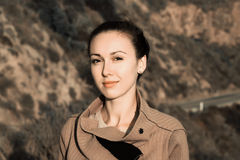 Portrait of a beautiful brunette. On a background of mountain road Stock Image