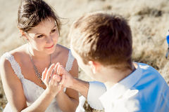 Portrait of beautiful brunette bride and her groom holding hands. Field on background.  Royalty Free Stock Images