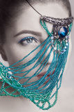Portrait of beautiful brunette fashion model white face skin color and blue makeup and red lips with blue jewelry in front of eye Royalty Free Stock Image