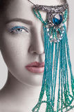 Portrait of beautiful brunette fashion model white face skin color and blue makeup and red lips with blue jewelry in front of eye Stock Photo