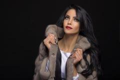 Portrait of a beautiful brunette in a fur coat Stock Photos