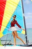 Portrait of beautiful brunette girl holds boat sails and smiling Stock Image