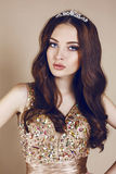 Portrait of beautiful brunette girl in luxurious sequin dress and crown. Fashion studio portrait of beautiful young girl with dark hair wearing luxurious beige royalty free stock image